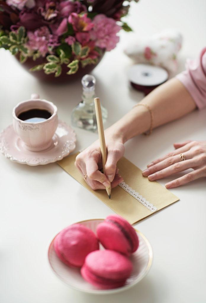 Dziewczyna adresuje kopertę ze ślubnym zaproszeniem